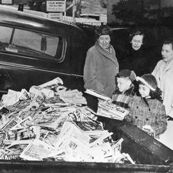 """John Chiangi and Lisa Drobnes add their comic book collection in the back of a pickup truck at Norwich, Conn., Feb. 26, 1955.  The Women's Auxiliary of the American Legion has scheduled a burning of such books, inviting children to bring in 10 books in exchange for a """"clean"""" book.  Looking on from left are, Mrs. Charles B. Gilbert, former national auxiliary president; Mrs. Edward Robinson; and Mrs. Webster Copp.  The scheduled bonfire brought protests from the American Civil Liberties Union and the American Book Publishing Council."""