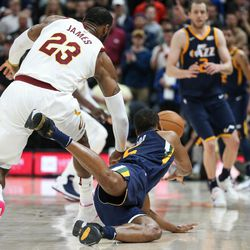 Utah Jazz guard Rodney Hood (5) moves the ball forward as he falls while moving against Cleveland Cavaliers forward LeBron James (23) at Vivint Arena in Salt Lake City on Saturday, Dec. 30, 2017.