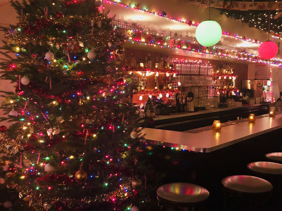 A Christmas tree stands next to a bar