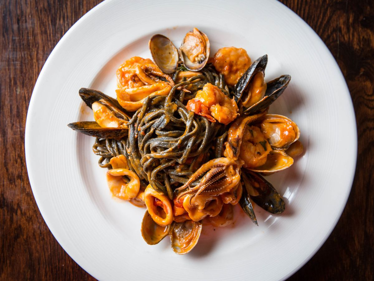 A plate of squid ink spaghetti and seafood.