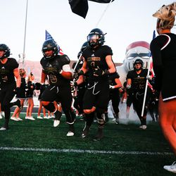 Lone Peak players take the field during a high school football game against Corner Canyon at Lone Peak High School in Highland on Thursday, Sept. 24, 2020.
