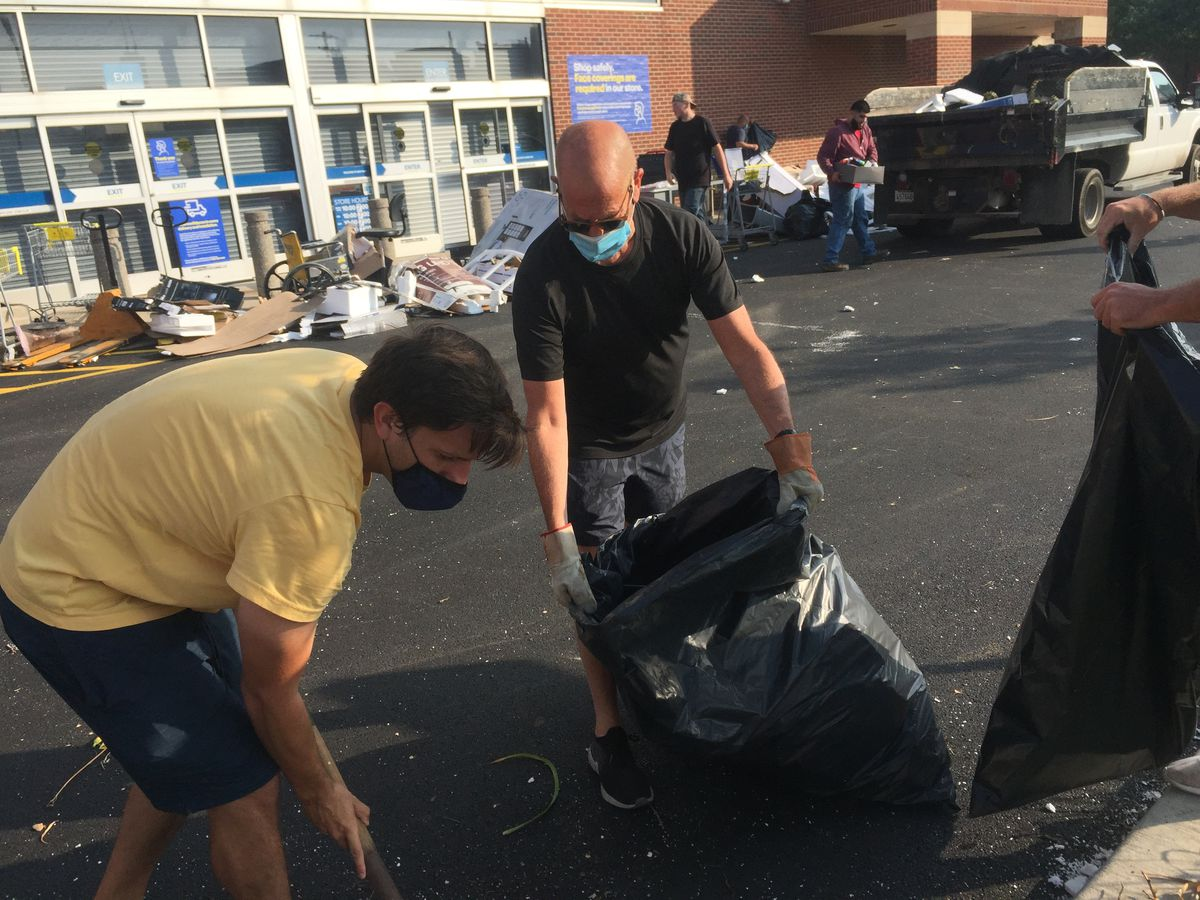 Bruce Alper, 66, of River North, center,helps clean up at a Best Buy near Marcey and Halsted streets.