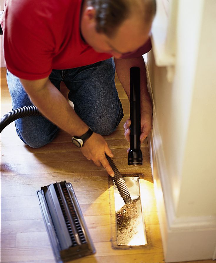 Person cleaning the floor vents as part of annual furnace cleaning.