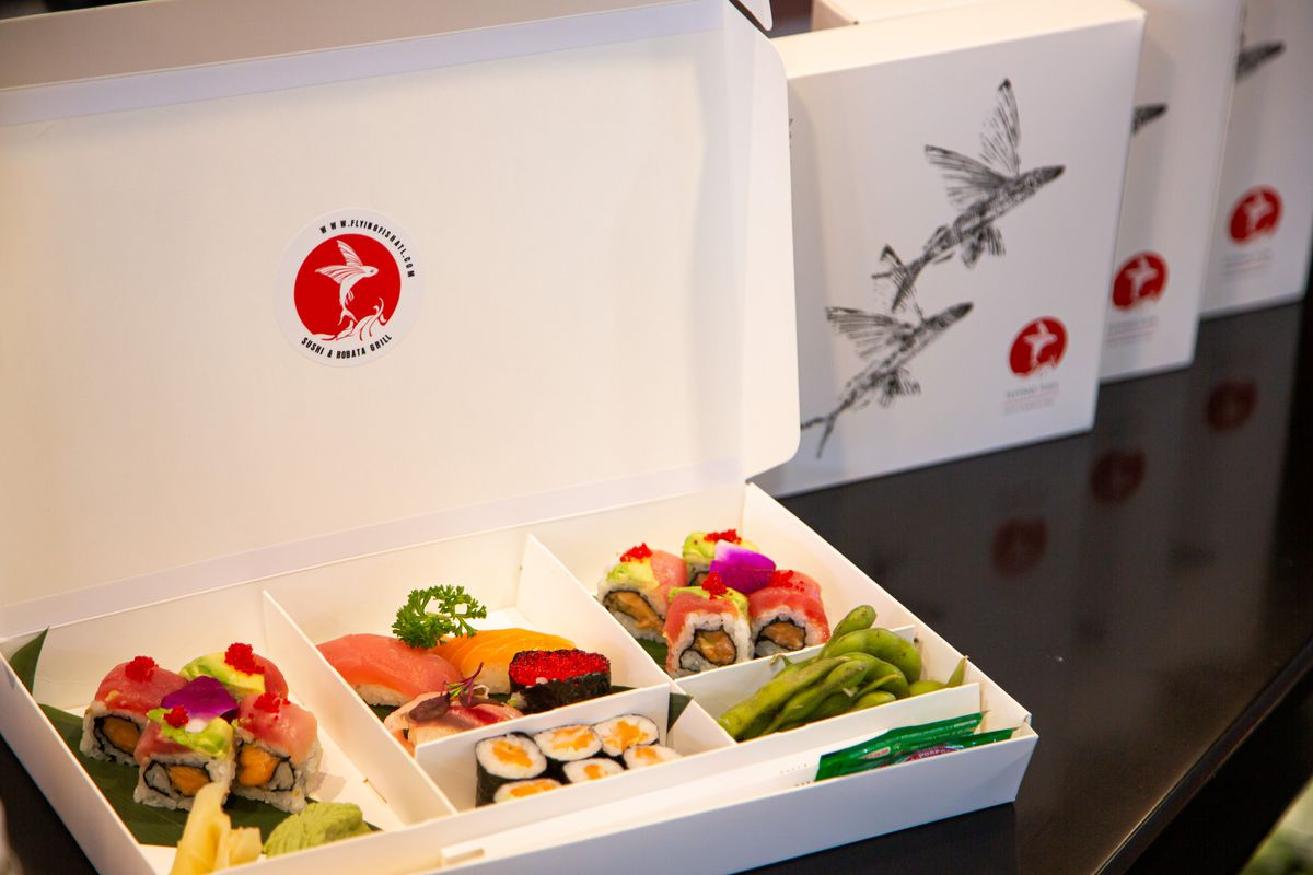 A white cardboard box containing colorful and neatly packed selection of sushi and sushi rolls from Flying Fish in Atlanta
