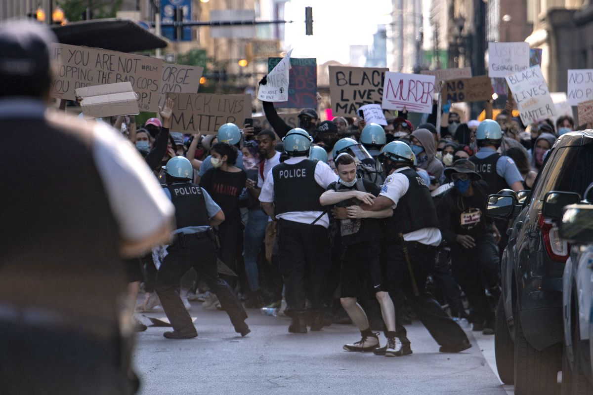 Chicago police and protesters scuffle near Daley Plaza on Saturday during a protest over the death of George Floyd, in police custody, in Minneapolis on Memorial Day.