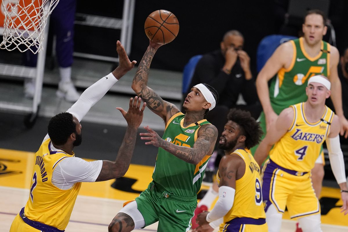 Utah Jazz guard Jordan Clarkson shoots over Los Angeles Lakers center Andre Drummond in an NBA game in Los Angeles in 2021.