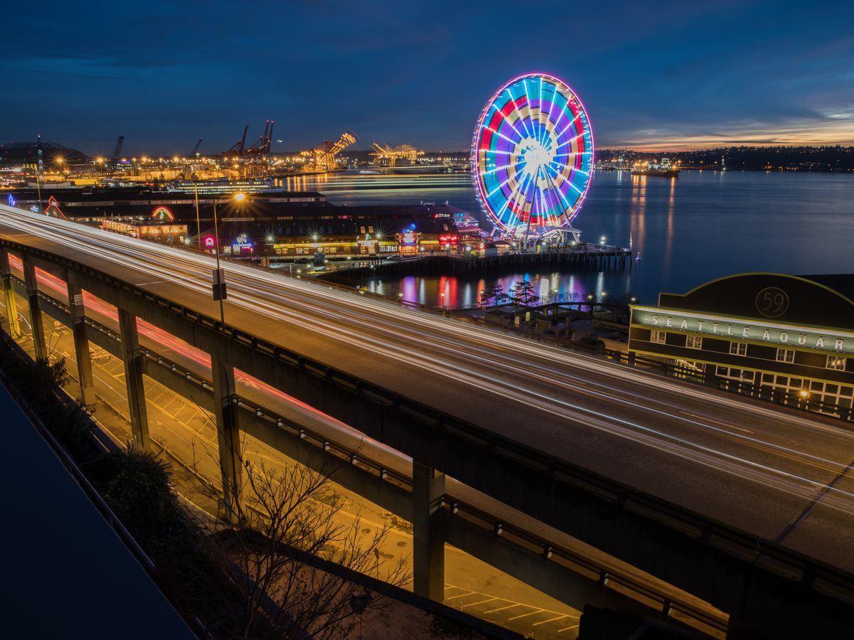 A large, double-decker, elevated highway runs along a coastline past many piers, including one with a lighted ferris wheel, at night.