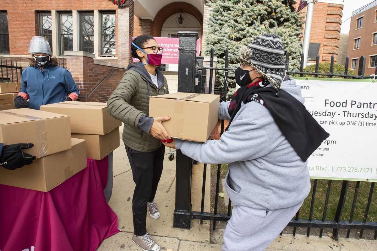 A woman in a pink mask hands a big cardboard box of food to a person in a grey sweatsuit and black winter hat