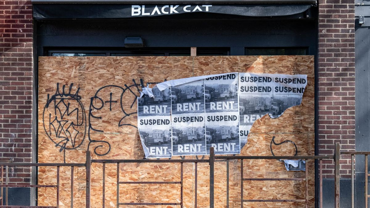 Flyers for rent suspensions appear on the front of Black Cat bar in Belltown