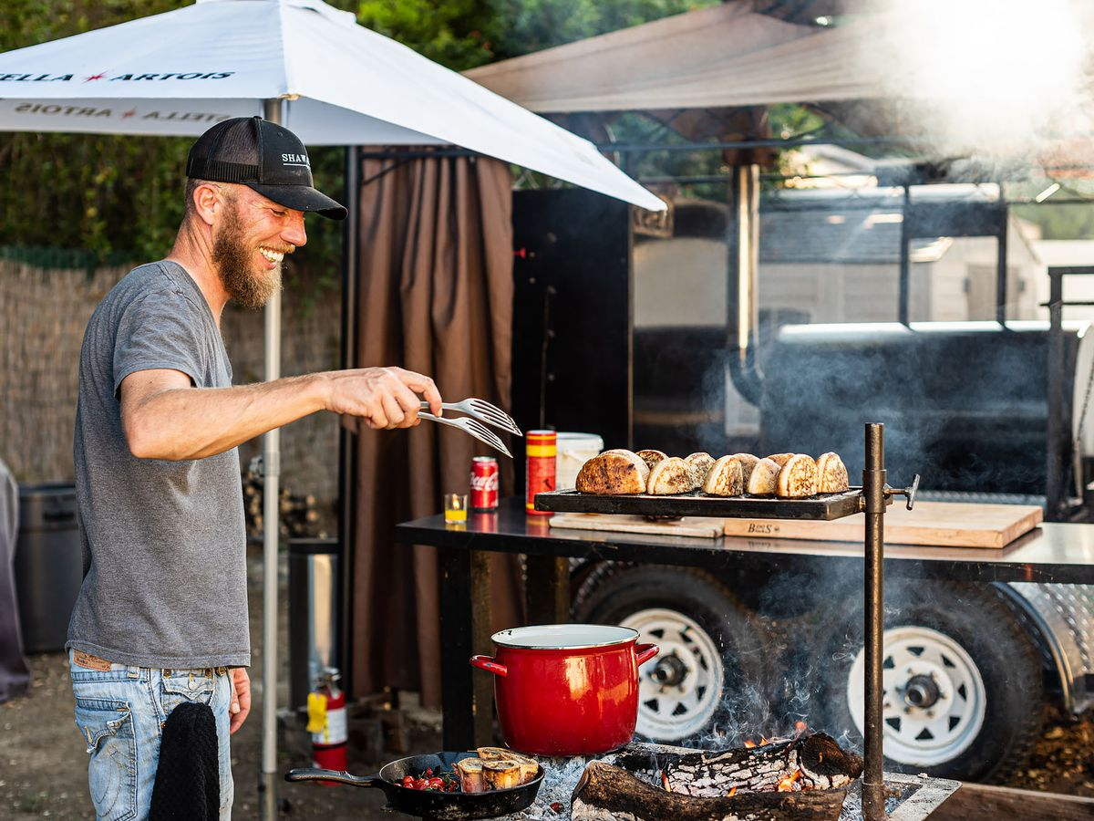 A tall, thin man works an open grill with meat sizzling.
