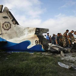 Nepalese police search through the debris at the crash site of a Sita Air airplane near Katmandu, Nepal, early Friday, Sept. 28, 2012.  The plane carrying trekkers into the Everest region crashed just after takeoff Friday morning in Nepal's capital, killing all 19 people on board, authorities said.