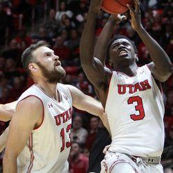 Utah Utes forward Donnie Tillman (3) goes up for a basket as forward David Collette (13) screens out Hawaii Warriors forward Mike Thomas (13) as Utah hosts Hawaii at the Huntsman Center in Salt Lake on Saturday, Dec. 2, 2017.