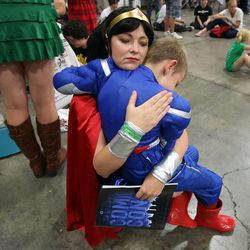 Laurisa Dixon, dressed as Wonder Woman, comforts her son Charlie, dressed as Captain America, after discovering that they missed the costume parade at Comic Con at the Salt Palace Convention Center in Salt Lake City on Saturday, Sept. 7, 2013.