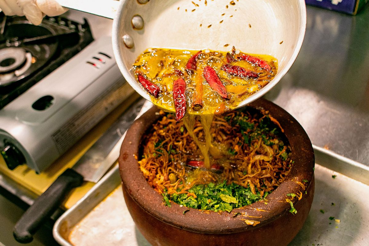 Someone pours Indian spices into a clay pot.