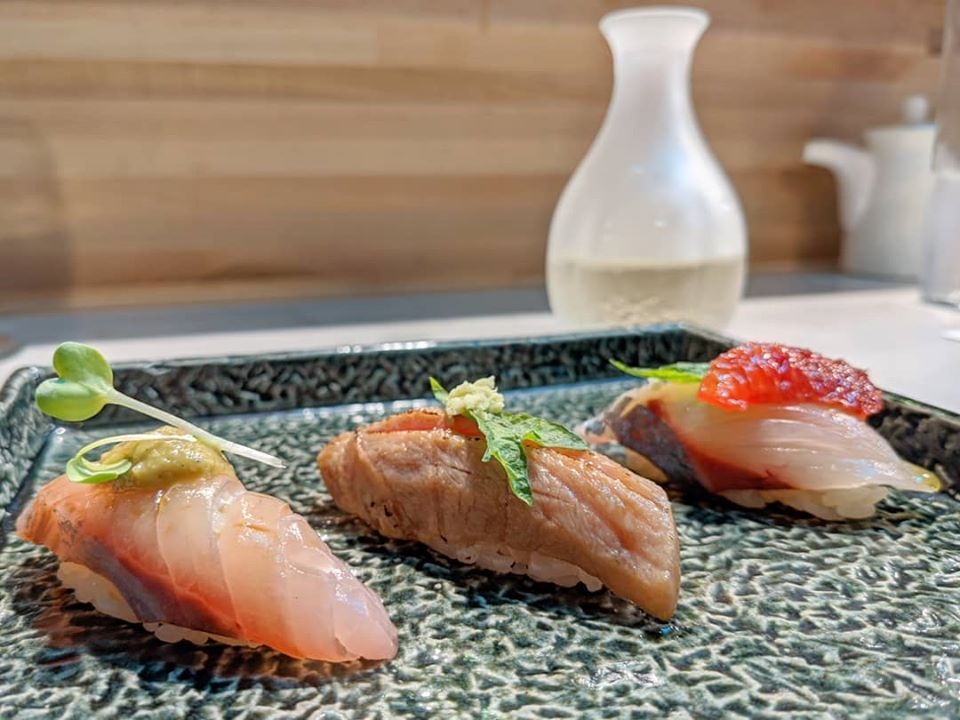Three pieces of sushi are lined up on a speckled blue-ish gray plate. A carafe of sake is visible in the background.