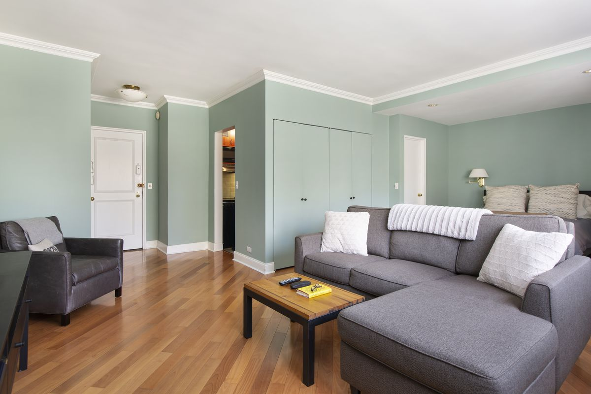 A living area with hardwood floors, light green walls, and a grey couch.