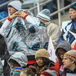As the rain begins to fall a  fan struggles to put on a rain poncho at the Zaxby's Heart of Dallas Bowl between the Utah Utes and the West Virginia Mountaineers in Dallas Texas on Tuesday, Dec. 26, 2017.