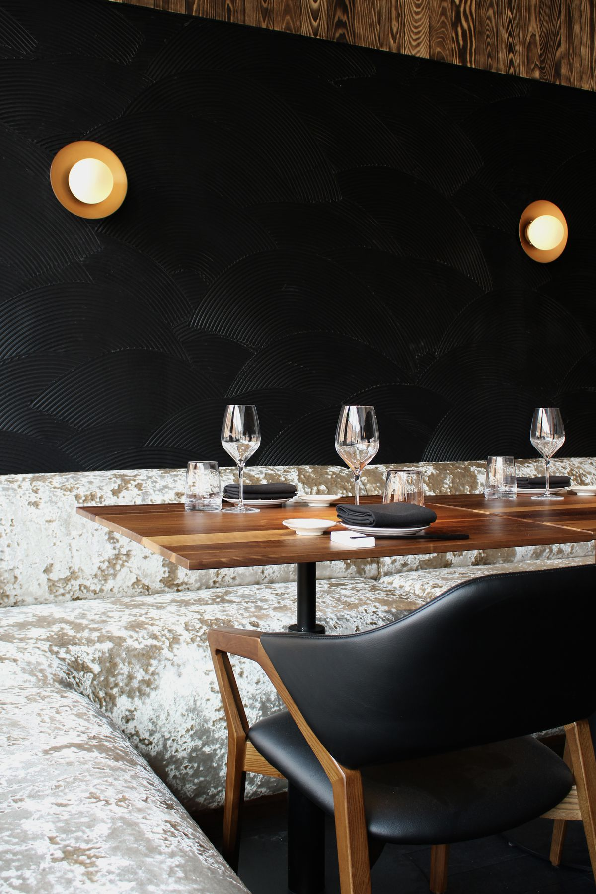 inside of restaurant with black walls and velvet booth seating