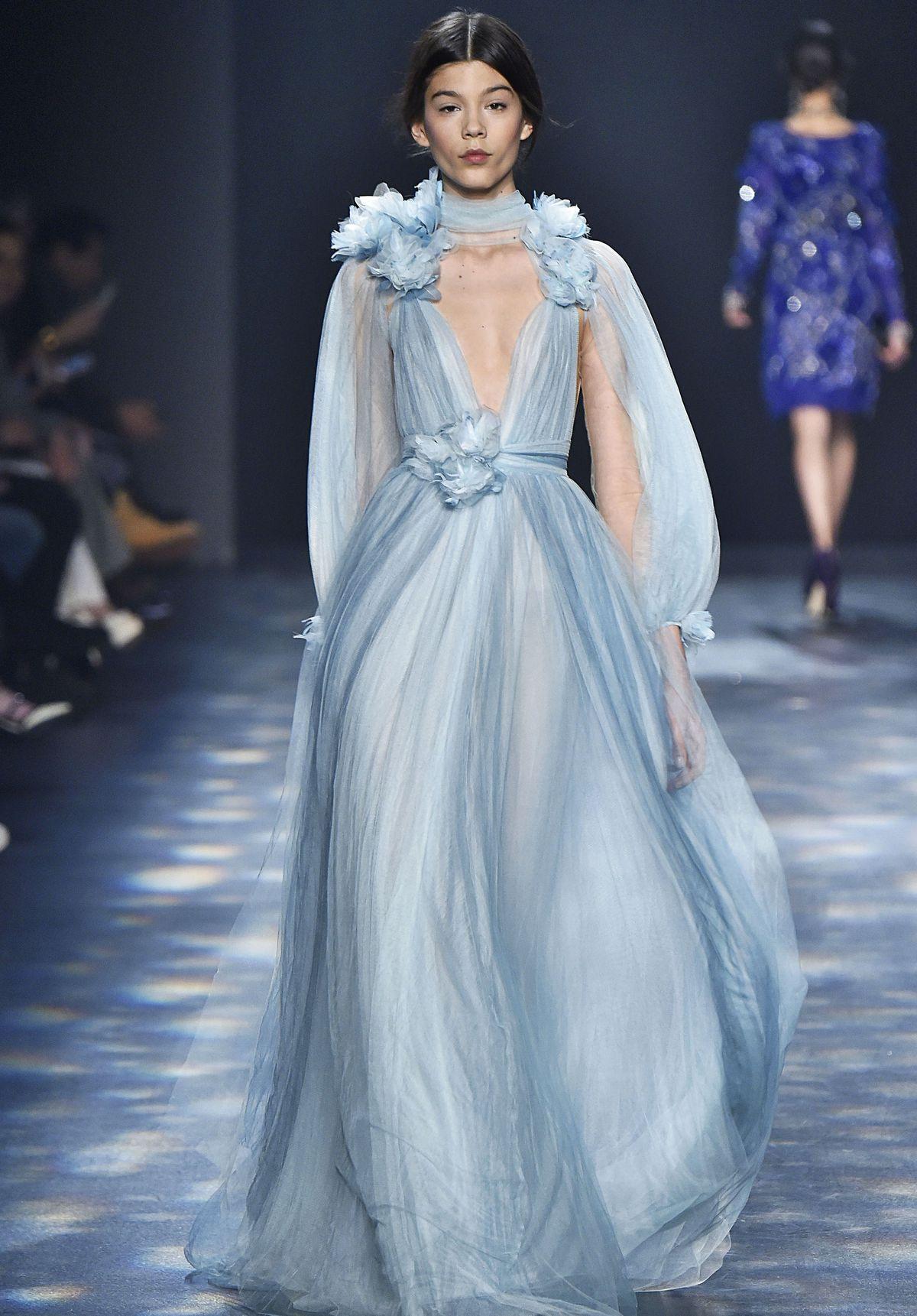 A model walks the runway wearing the blue dress.