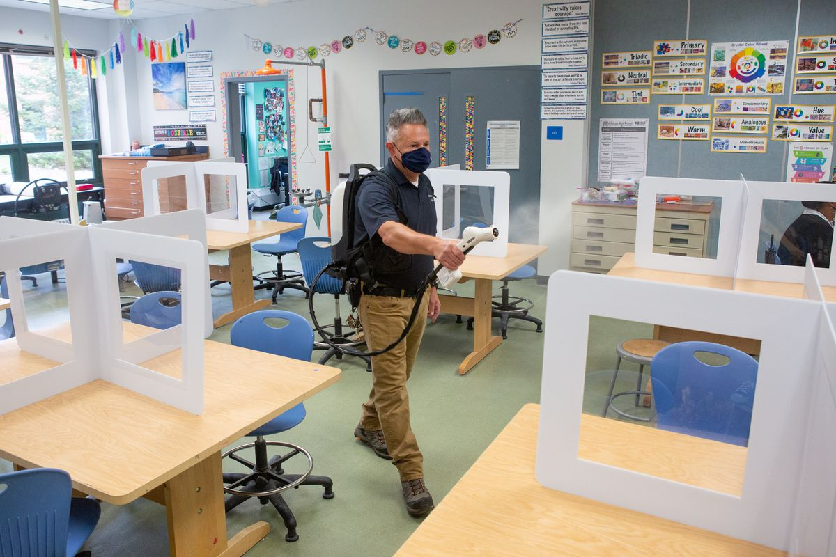 Janitorial staff member Jeffrey Turro uses a disinfectant spray gun to clean a classroom.