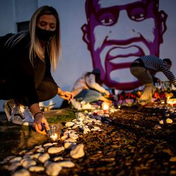 Misti Western lights candles in front of a mural of George Floyd in Salt Lake City after a jury found former Minneapolis police officer Derek Chauvin guilty in the killing of Floyd on Tuesday, April 20, 2021.