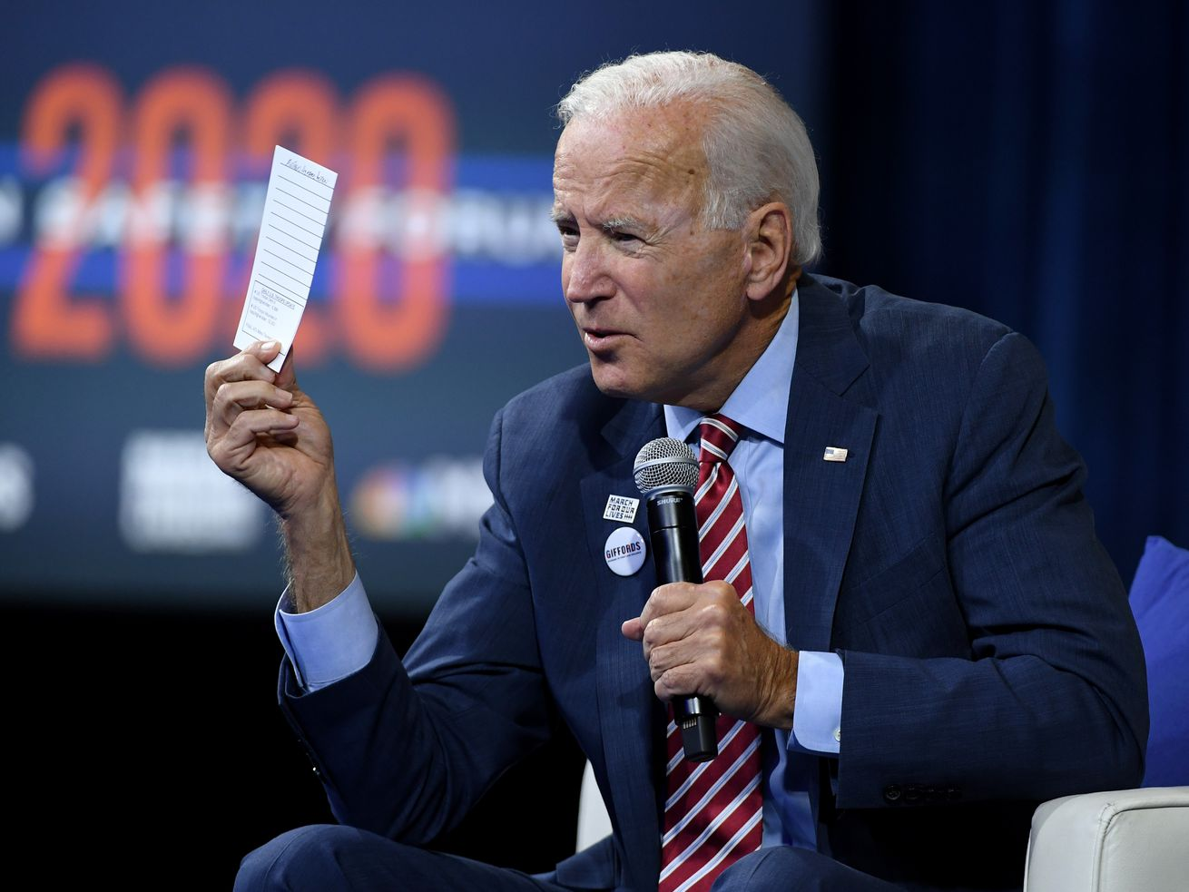 Former Vice President Joe Biden on stage at an event in Las Vegas sitting down.