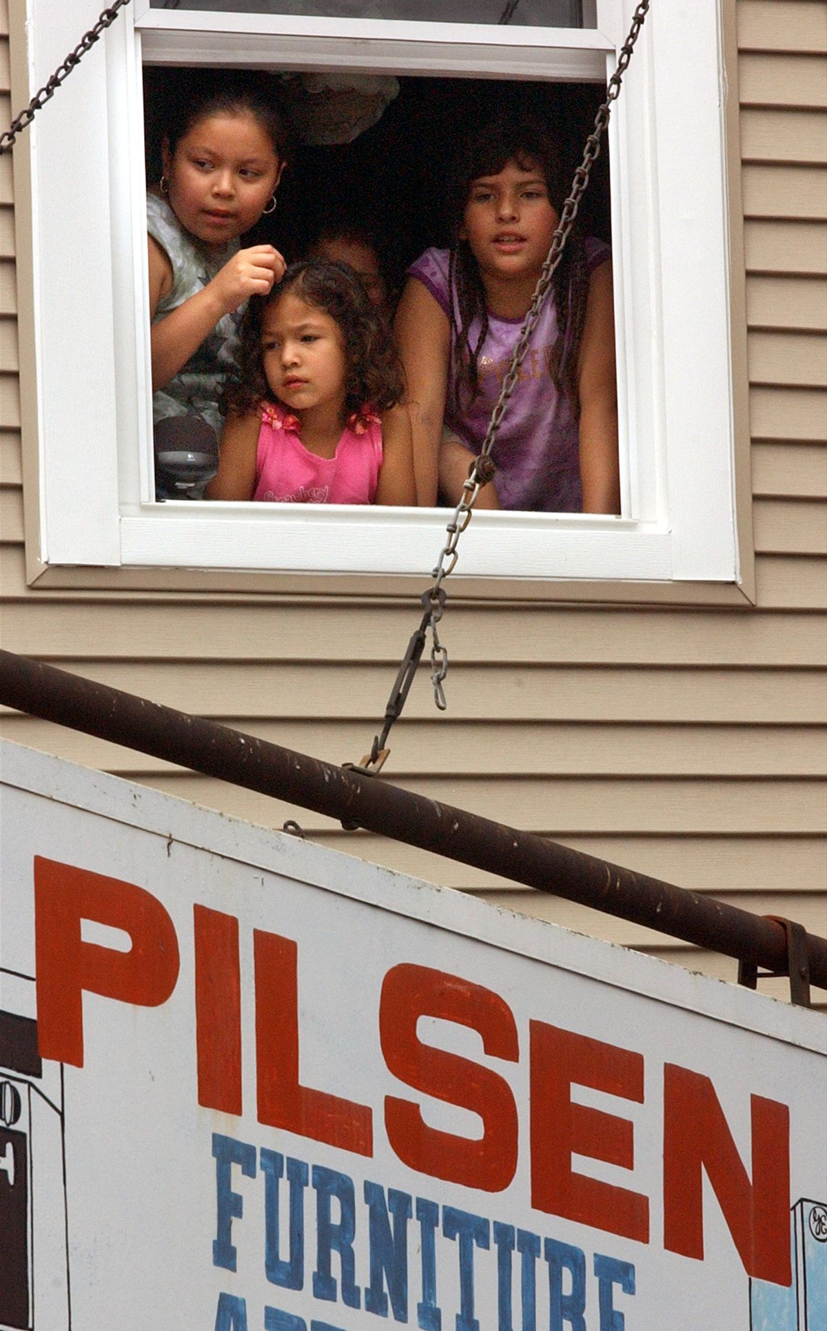 9-5-04 Annual Mexican Independence Day walked from Loomis & 18th street to Damen Street along 18th street thru the Pilsen neighborhood and thousands came out to greet the parade marchers and floats... here ..... kids watch from a 2nd floor window