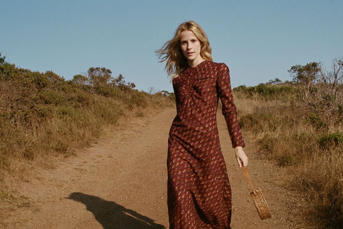 A woman in a burgundy long-sleeved maxi dress