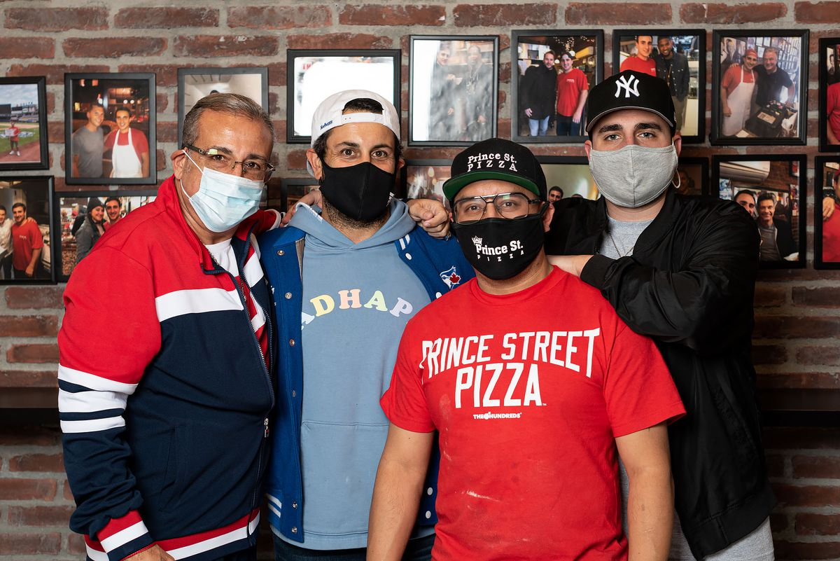 A restaurant family stands with masks on inside.