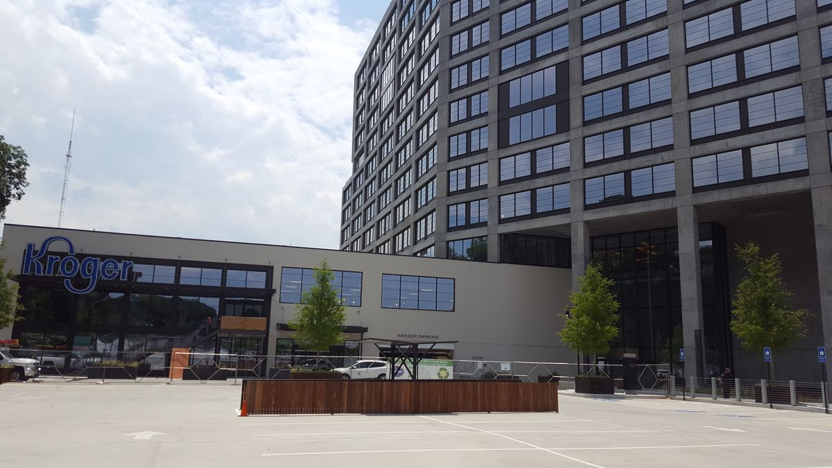 A beige Kroger sits in the shadow of the glassy, 12-story office building.