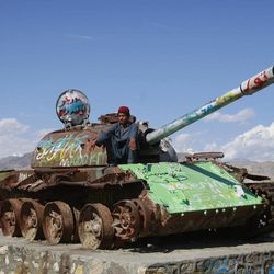 An Afghan sits on top of an old Soviet tank in the outskirts of Kabul, Afghanistan, Thursday, April 12, 2012.