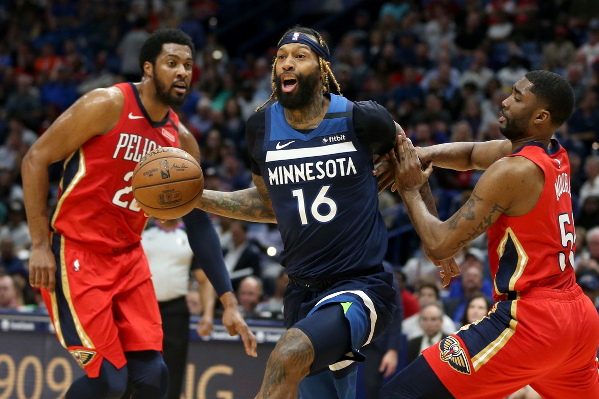 Minnesota Timberwolves forward James Johnson is defended by New Orleans Pelicans guard E'Twaun Moore in the second quarter at the Smoothie King Center.