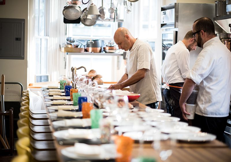 chef working at a long table set for a meal