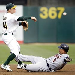 Oakland Athletics' Mark Ellis, left, throws to first base after forcing out Detroit Tigers' Carlos Guillen, right, on Miguel Cabrera's fielders choice.