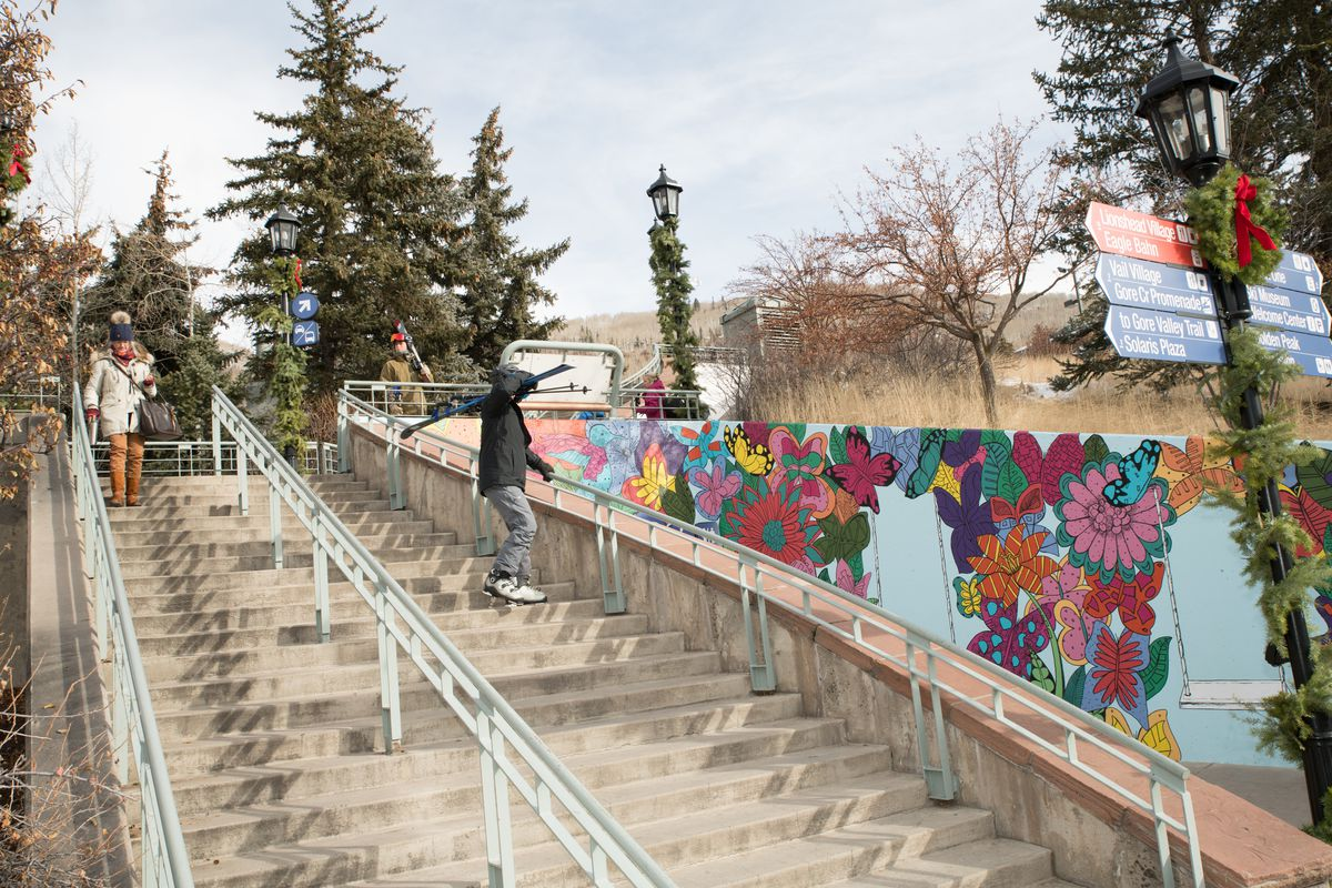 A bright colored mural with flowers and butterflies on the side of a staircase.