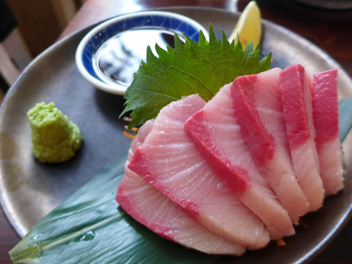 Thick slices of fish, a shiso leaf, soy soy in a small vessel, and a mound of green wasabi.