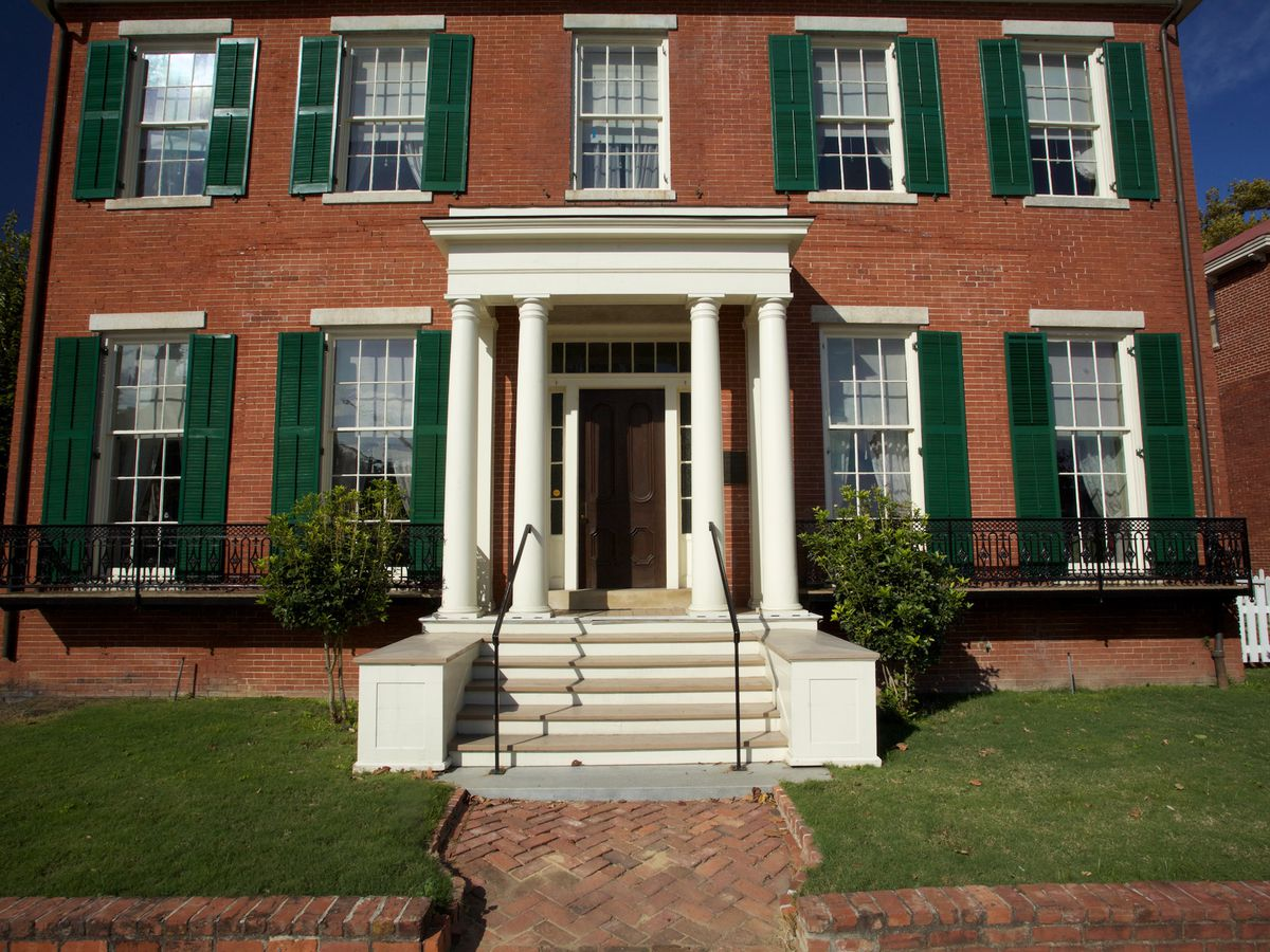The exterior of the boyhood home of President Woodrow Wilson. The facade is red brick with white columns near the entrance. The windows have green shutters.