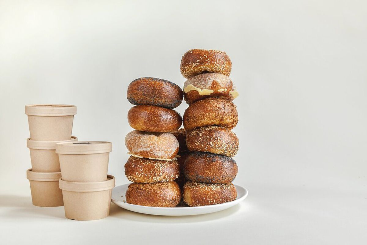 A tower of bagels from Mt Bagel, with containers of cream cheese on the side.