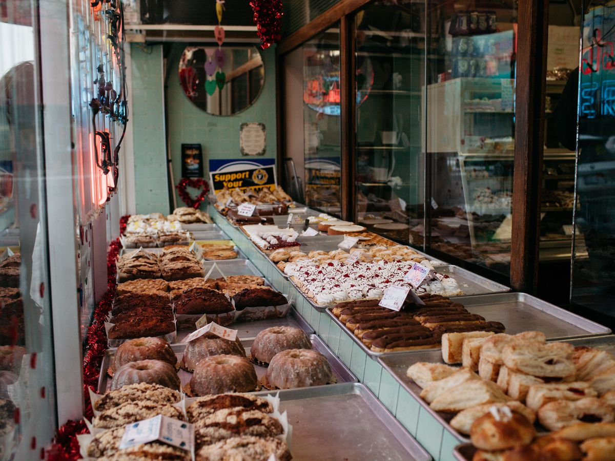 Pastries and bunt cakes sit in a window display at New Palace Bakery.