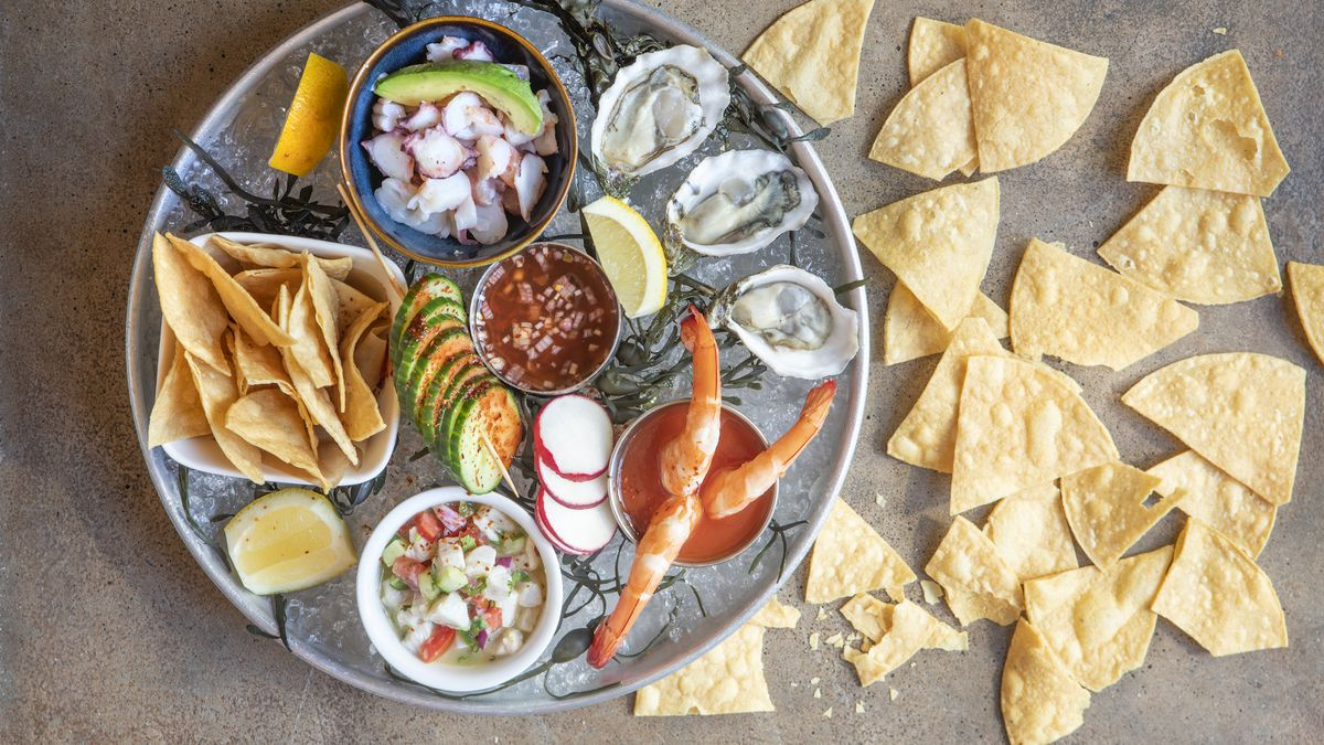 A platter of seafood with tortilla chips spread around.