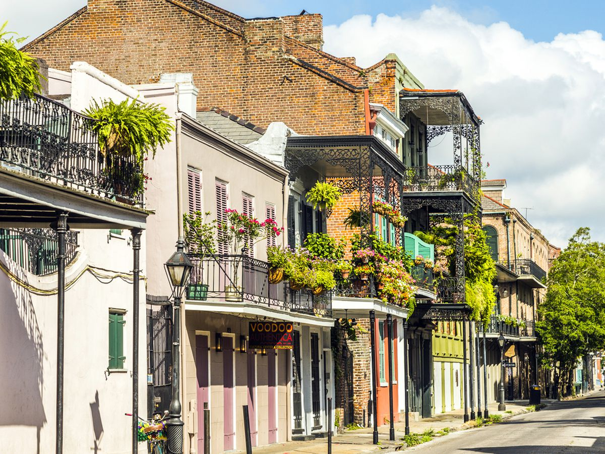A row of two-story brick townhomes with plant-hung balconies in the French Quarter of New Orleans