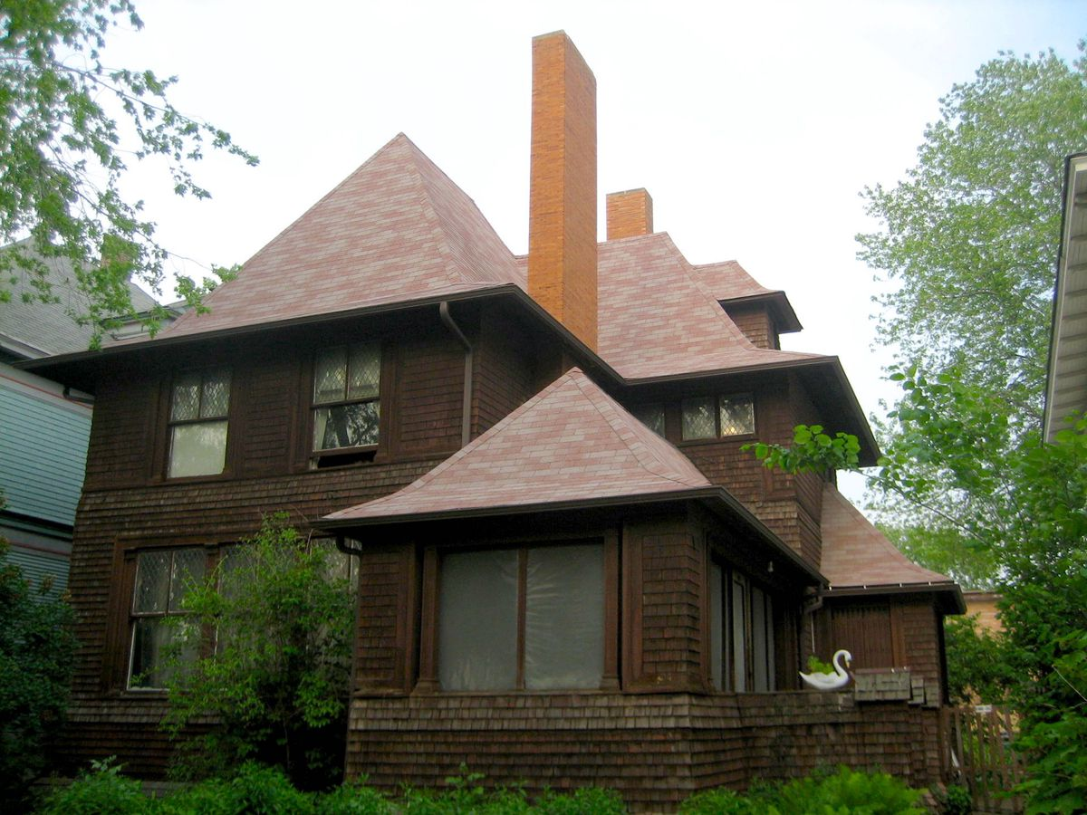 The exterior of a house with a brown facade and multiple roofs.