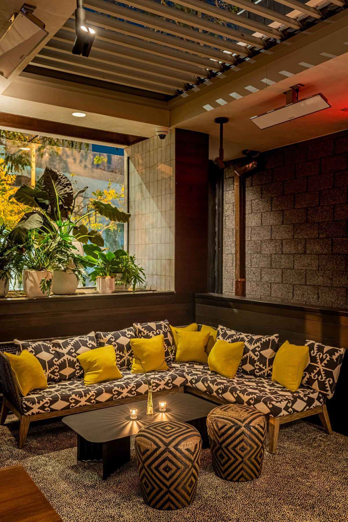 A corner lounge area at night inside of an open-air bar, with yellow pillows.