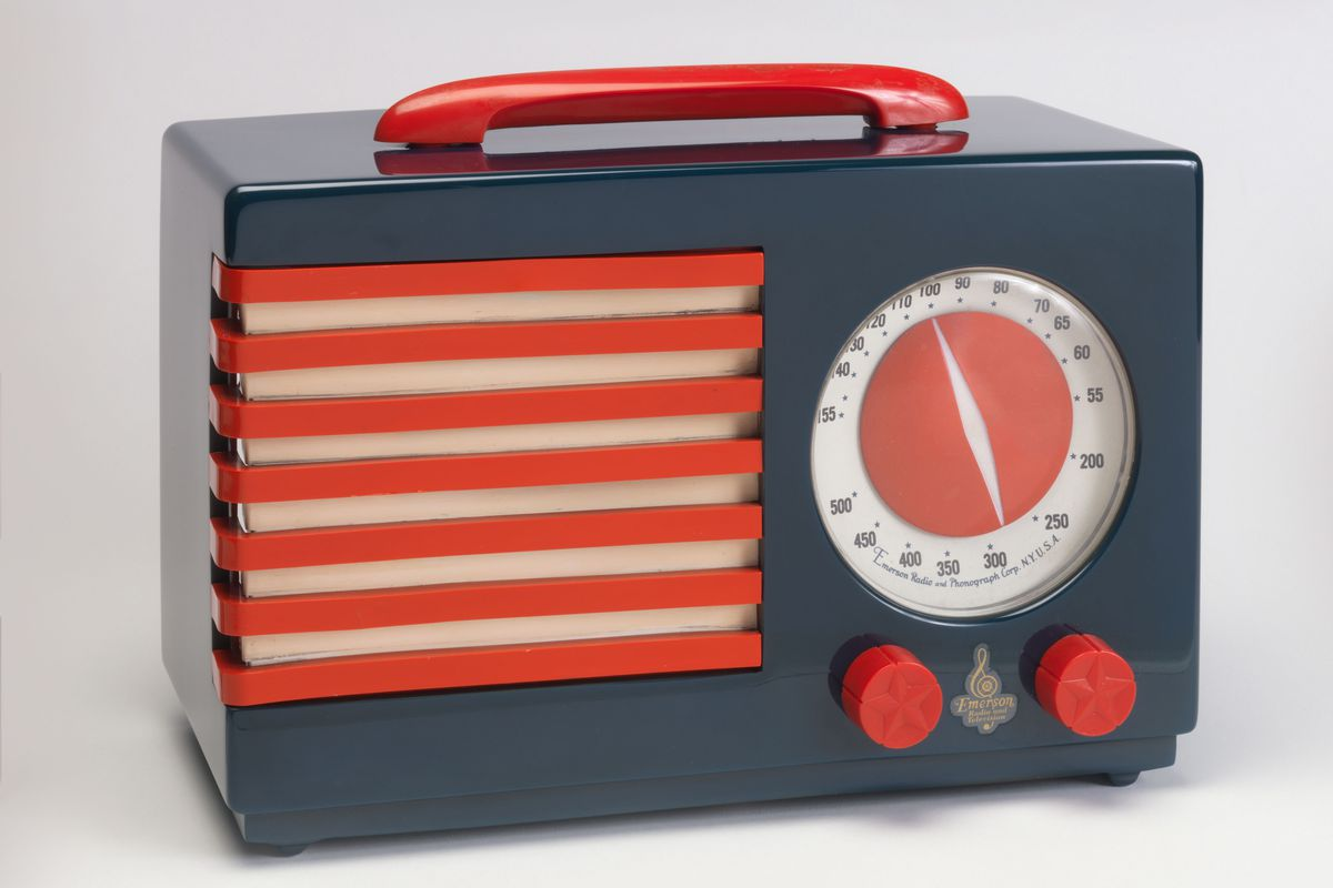 A portable radio with a red handle on top, two knobs and a round dial. The body is dark gray, the speaker is red and white striped, with red knobs and handle.