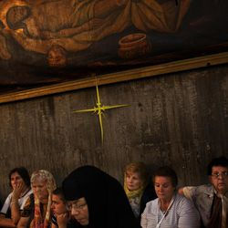 Greek Orthodox worshippers attend a vesper ceremony inside the Church of the Holy Sepulchre, traditionally believed to be the burial site of Jesus Christ, in Jerusalem's Old City, Saturday, April 7, 2012. (AP Photo/Bernat Armangue)