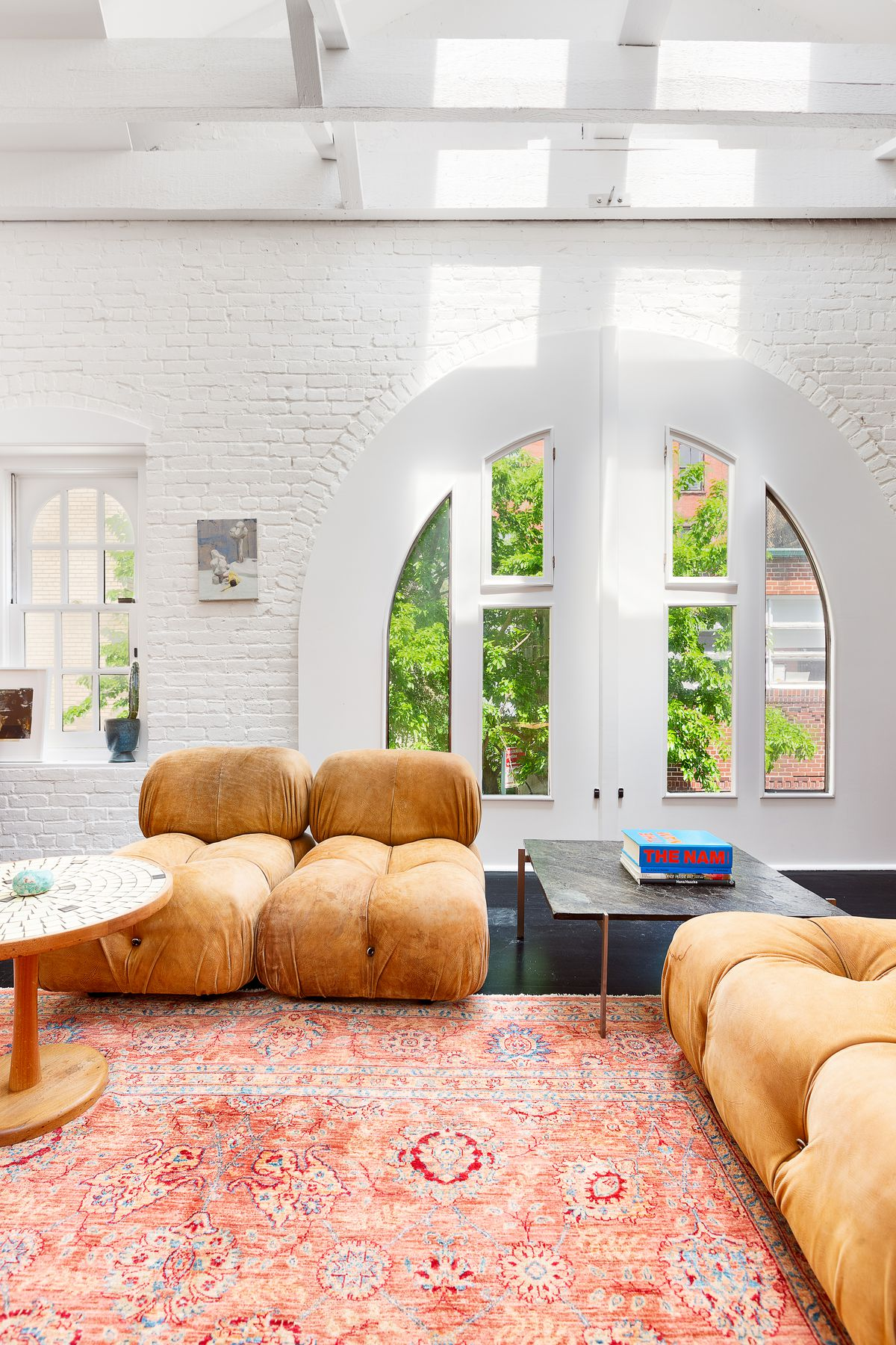 A living area with an arched window, brown couches, and a red rug.