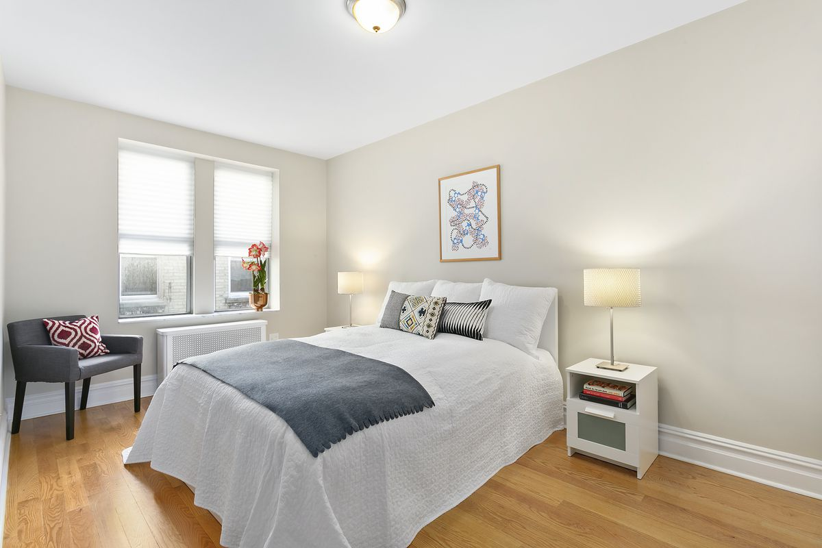 A bedroom with a medium-sized bed, hardwood floors, beige walls, and two windows.
