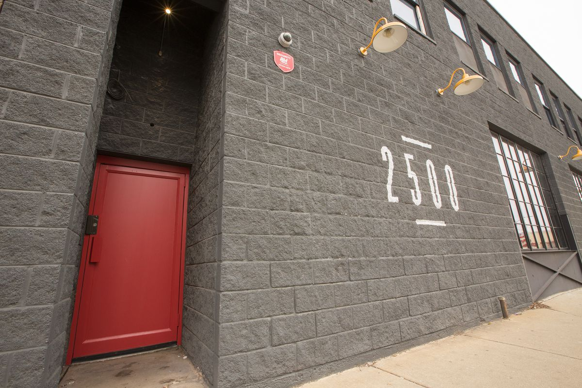 A red door in between gray brick walls.