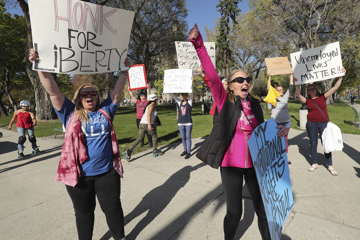 """Kassity Norris and her mother, Barbara Norris, shout at motorists as the group """"Freedom in the Numbers! No More Social Distance!"""" rallies against a state stay-at-home request at the Salt Lake City-County Building in Salt Lake City on Saturday, April 18, 2020."""