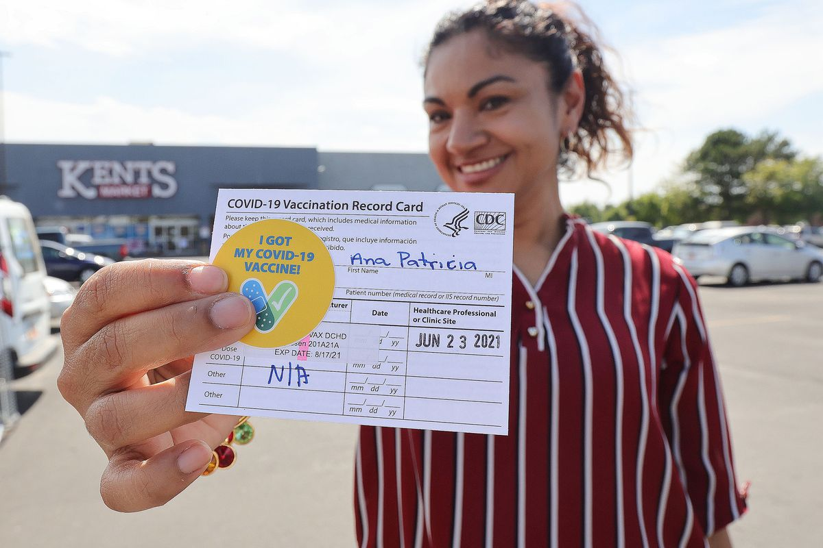 Ana Patricia Jenkins holds her vaccination record card in Utah.
